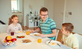 Lycklig fader med hans barn som hemma talar på frukosten arkivfoto