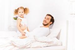 Lycklig fader med hans dotter i vit pyjamas royaltyfria bilder