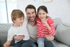 Lycklig fader med hans hemmastadda ungar ha gyckel Arkivfoto