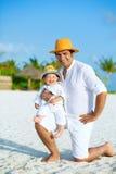 Lycklig fader med sonen på stranden Arkivfoto