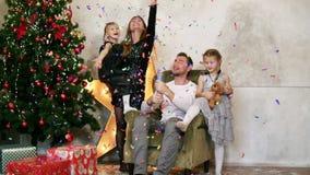 Lycklig fader, moder och två döttrar som tillsammans firar jul Gullig familj av fyra som har gyckel med petards arkivfilmer