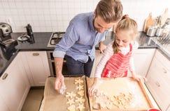 Lycklig fader och dotter som förbereder kakor för att baka i kitchen arkivfoto