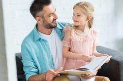 lycklig fader och dotter som ler sig medan läsebok tillsammans fotografering för bildbyråer