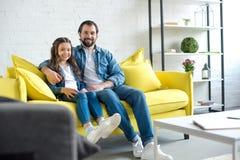 lycklig fader och dotter som tillsammans sitter på den gula soffan och att le arkivbild