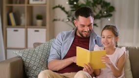 Lycklig fader- och dotterläsebok hemma stock video
