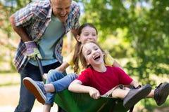 Lycklig fader och hans barn som spelar med en skottkärra Arkivbilder