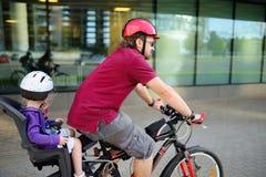 Lycklig fader och hans liten litet barndotter som tillsammans rider en cykel Arkivfoton