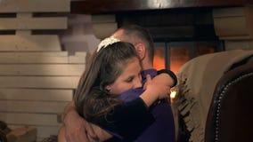 Lycklig fader och liten dotter som omfamnar sig på fåtöljen nära spisen arkivfilmer