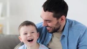 Lycklig fader och liten son som hemma skrattar