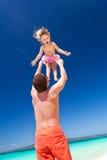 Lycklig fader och litet barn på stranden Arkivbild