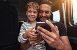 Lycklig fader och son baktill av bilen med den digitala minnestavlan Royaltyfria Bilder