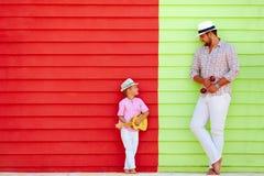 Lycklig fader och son med musikinstrument nära den färgrika väggen Royaltyfri Bild