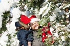Lycklig fader och son som bär en hatt av Santa Claus och som sätter en sörja arkivbilder