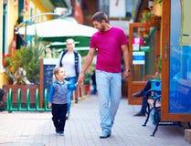Lycklig fader och son som går stadsgatan Arkivfoton