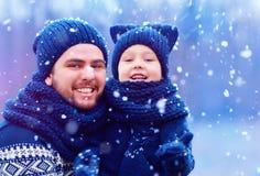 Lycklig fader och son som har gyckel under vintersnö, semesterperiod Arkivbild