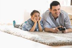 Lycklig fader och son som hemma spelar videospelet på golv royaltyfria foton