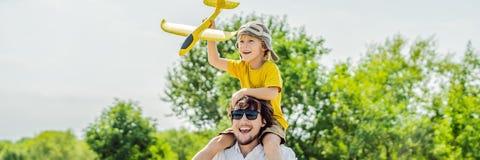 Lycklig fader och son som spelar med leksakflygplanet mot gammal landningsbanabakgrund Resa med ungebegreppsBANRET, LÅNGT FORMAT royaltyfri fotografi