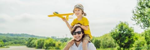 Lycklig fader och son som spelar med leksakflygplanet mot gammal landningsbanabakgrund Resa med ungebegreppsBANRET, LÅNGT FORMAT arkivbild