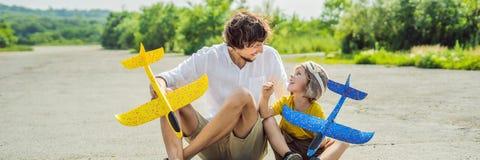 Lycklig fader och son som spelar med leksakflygplanet mot gammal landningsbanabakgrund Resa med ungebegreppsBANRET, LÅNGT FORMAT royaltyfria foton