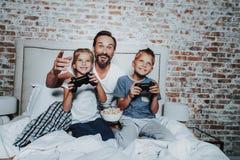 Lycklig fader och ungar som spelar med den modiga konsolen arkivbilder