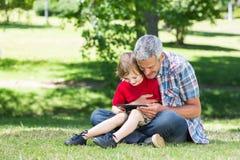 Lycklig fader som använder minnestavlaPC med hans son Royaltyfri Fotografi