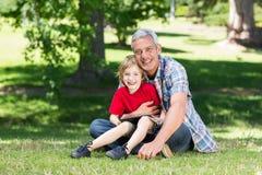 Lycklig fader som använder minnestavlaPC med hans son Fotografering för Bildbyråer