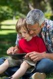 Lycklig fader som använder minnestavlaPC med hans son Arkivfoton