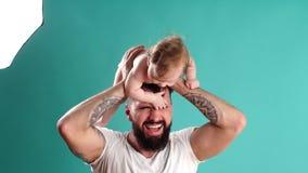 Lycklig fader som bär hans begynnande dotter på halsen som isoleras över blå bakgrund arkivfilmer