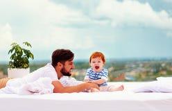 Lycklig fader som framme spelar med den begynnande sonen i säng av fönstret royaltyfri foto