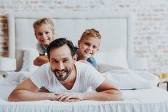 Lycklig fader som lägger på säng med två ungar royaltyfria foton