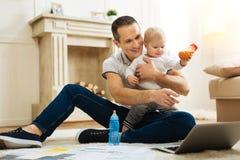 Lycklig fader som pekar till skärmen medan hans barn som rymmer en flaska Arkivbild