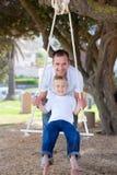 Lycklig fader som skjuter hans son på en swing Royaltyfri Fotografi