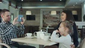 Lycklig fader som tar fotoet av hans fru som kysser deras dotter vid smartphonen på restaurangen lager videofilmer