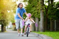 Lycklig fader som undervisar hans lilla dotter att rida en cykel Barn som lär att rida en cykel royaltyfria foton