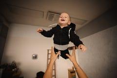 Lycklig fader som upp kastar i luften hans gulliga lilla son Arkivbild