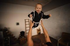 Lycklig fader som upp kastar i luften hans lilla son Arkivbild