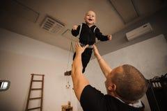 Lycklig fader som upp kastar i luften hans son Royaltyfria Bilder