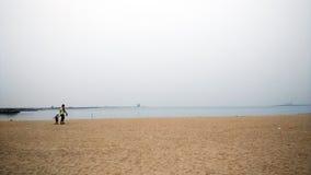 Lycklig faderinnehavhand av den lilla sonen som tillsammans går på stranden med skor Royaltyfria Foton