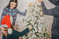 Lycklig fadermoder och hans liten dotter som hemma dekorerar julgranen Royaltyfri Foto
