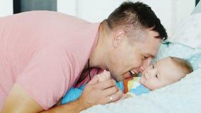 lycklig faderskap Den unga attraktiva mannen ler på hans unga son stock video