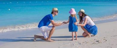 Lycklig familj av den tyckande om semestern för strand tre Arkivbilder
