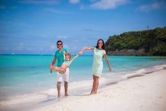 Lycklig familj av den tyckande om semestern för strand tre Royaltyfri Bild