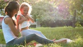 Lycklig familj av den unga sportiga modern och lilla gulliga dottern som har roligt utomhus lager videofilmer