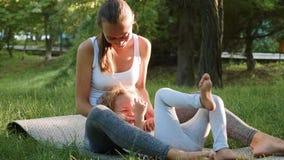 Lycklig familj av den unga sportiga modern och lilla gulliga dottern som har roligt utomhus stock video