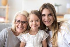Lycklig familj av farmodern, dottern och barnet som ser camer royaltyfri bild