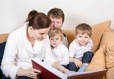 Lycklig familj av fyra hållande ögonen på gammala foto hemma. Royaltyfri Foto