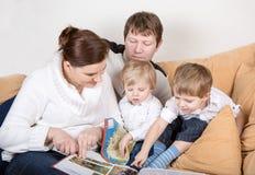 Lycklig familj av fyra hållande ögonen på gammala foto hemma. Royaltyfri Bild