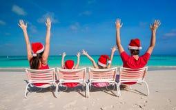 Lycklig familj av fyra i julhattar under Royaltyfria Bilder