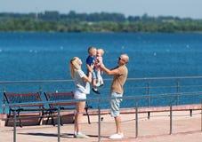 Lycklig familj av fyra på stenbryggan vid floden Royaltyfri Fotografi