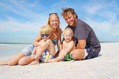 Lycklig familj av fyra på stranden Royaltyfria Bilder